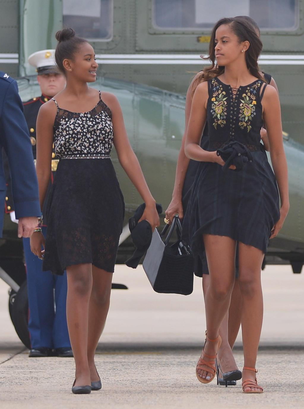 Sasha (L) and Malia (R), the daughters of US President Barack Obama and First Lady Michelle Obama, make their way to board Air Force One before departing from Andrews Air Force Base in Maryland on August 30, 2014. Obama is returning to Westchester County, New York to attend the wedding of his personal chef Sam Kass. AFP PHOTO/Mandel NGAN (Photo credit should read MANDEL NGAN/AFP/Getty Images)